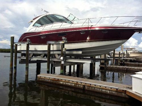 Red and white boat on a 56,000 pound 8 Post Boat Lift installed on Fort Myers Beach.