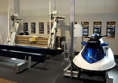 Boat lift and pwc lift holding a blue and white jet ski in a display room.