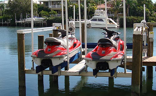 Two red jet skis on a pwc lift.