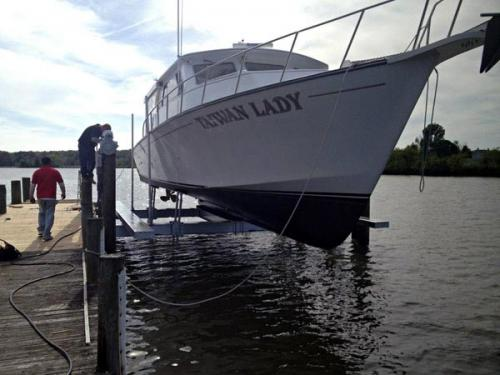 Front view of a white and black boat on a 40,000 pound 8 post boat lift installed in Ocean City, Maryland.