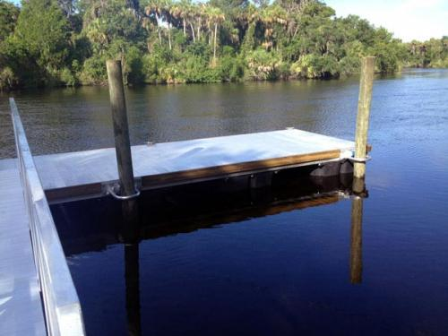 grey aluminum floating dock in water at a 90 degreen angle