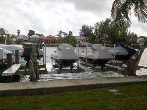 Front view of Four gray jet skis on a custom pwc lift.