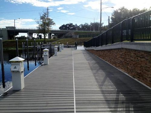 wide floating aluminum dock beside large cement walkway with railing