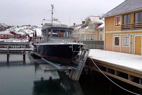 Elevator lift holding black boat on a snowy day