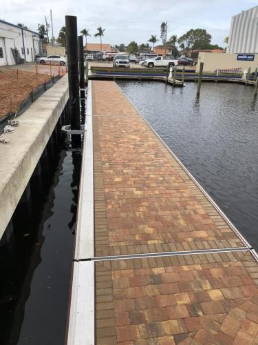angled shot of brick textured floating aluminum dock on water