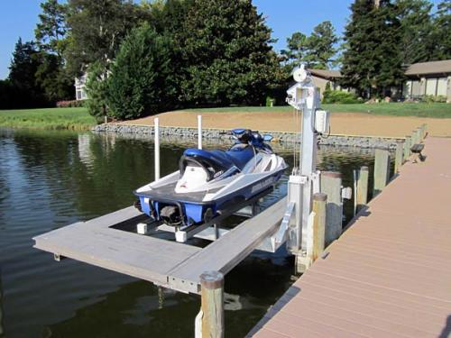 Blue and white jet ski on a pwc lift with decking.