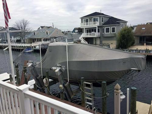covered boat on elevator lift in residential area