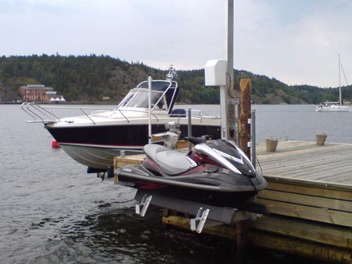 Black, red and white jet ski on a pwc lift with a black and white boat in the background.
